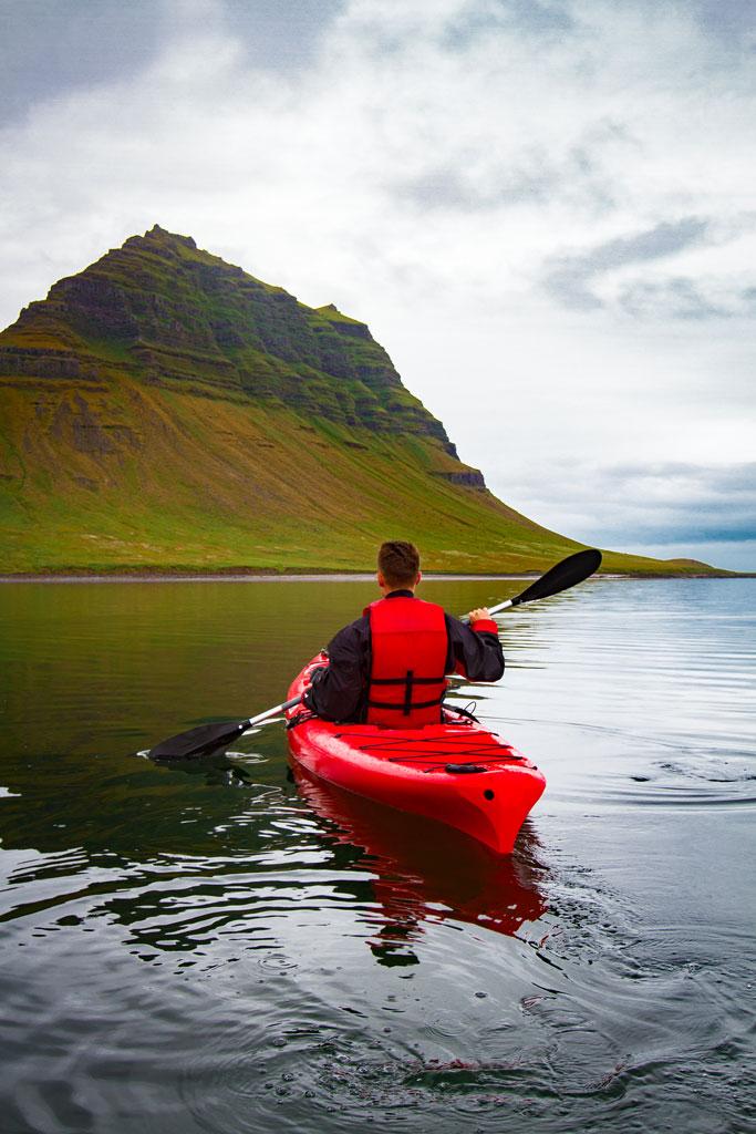 Kayaking in sea arounf kirkjufell mountain iceland