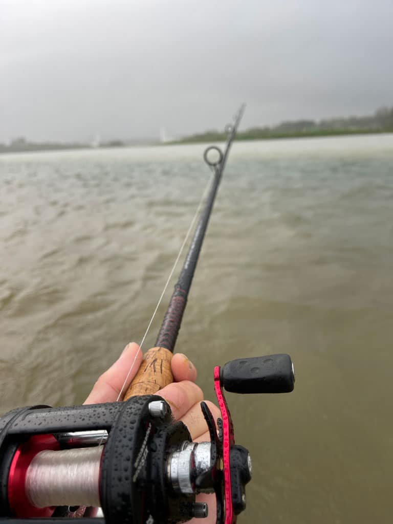 man holding fishing rod fishing in iceland